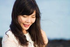 女孩在海滩的岩石站立 免版税图库摄影