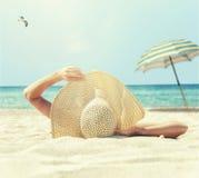 女孩在海滩的白色沙子说谎 库存照片