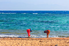 女孩在海洗他们的脚 免版税库存照片