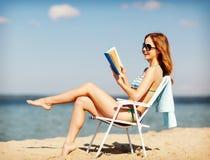 女孩在海滩睡椅的阅读书 免版税库存照片