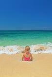 女孩在海洋碎波坐沙子海滩 免版税库存照片