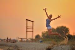 女孩在海滩跳 免版税库存照片