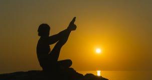 女孩在海洋附近实践瑜伽 免版税库存照片