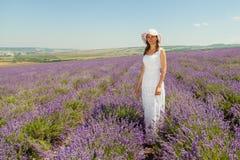 女孩在淡紫色领域走 免版税图库摄影