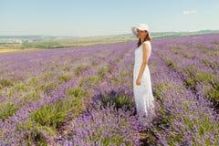 女孩在淡紫色领域走 图库摄影