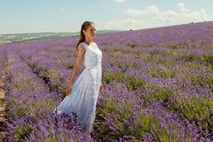 女孩在淡紫色领域走 免版税库存照片
