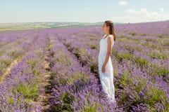 女孩在淡紫色领域走 库存图片