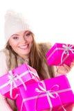女孩在温暖的冬天穿衣与许多桃红色礼物盒 免版税图库摄影