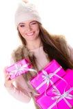 女孩在温暖的冬天穿衣与许多桃红色礼物盒 免版税库存图片