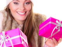 女孩在温暖的冬天穿衣与许多桃红色礼物盒 库存照片