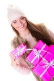 女孩在温暖的冬天穿衣与许多桃红色礼物盒 免版税库存照片