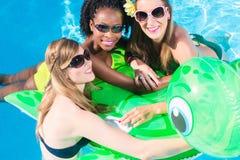 女孩在游泳池中水与可膨胀anmimal的 免版税库存图片