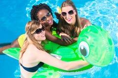 女孩在游泳池中水与可膨胀anmimal的 免版税库存照片