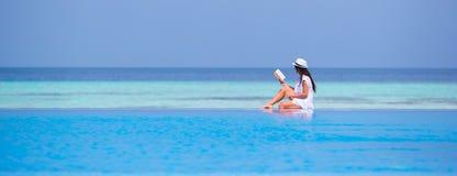 女孩在游泳池附近的阅读书 免版税图库摄影