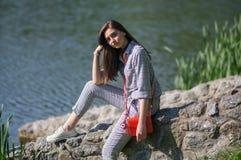 女孩在湖附近坐 库存照片