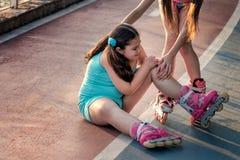 女孩在溜冰鞋,膝盖痛苦跌倒了,室外 免版税库存图片