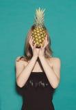 女孩在演播室拿着手菠萝,盖她在一件黑礼服的自己的面孔在绿色背景 概念 库存图片