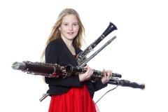 女孩在演播室拿着木管乐器 免版税库存照片