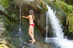 女孩在瀑布附近站立 免版税库存照片