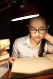 女孩在灯下的阅读书 免版税库存照片