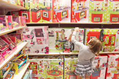 女孩在玩具商店选择一个玩具 免版税库存图片