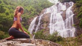 女孩在瑜伽位置休息在泡沫似的瀑布特写镜头附近 股票视频
