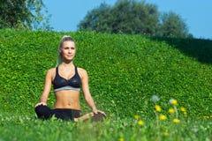 女孩在瑜伽位置思考 免版税库存图片