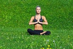 女孩在瑜伽位置思考 免版税库存照片