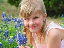 女孩在用花装饰的草甸 图库摄影