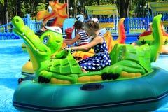 女孩在电筏乘坐在城市公园 免版税库存图片