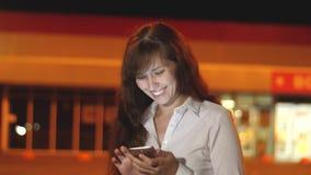 女孩在电话使用流动互联网在夜城市 股票录像
