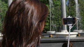 女孩在电话和一根selfie棍子做一张照片,在一个喷泉的背景在公园,看法从后面 股票视频