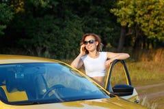 女孩在电话谈话乘汽车 库存照片