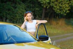 女孩在电话谈话乘汽车 免版税库存图片
