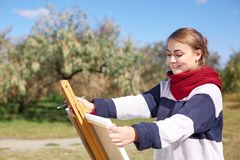 女孩在画架画反对清楚的天空背景  免版税库存图片