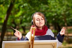 女孩在画架画并且听到音乐 库存照片