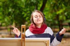 女孩在画架画并且听到音乐 免版税库存图片