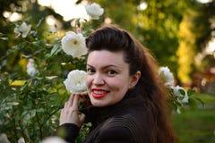 女孩在白玫瑰庭院(少妇画象里) 免版税库存照片