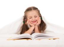 女孩在白色床上读了书 库存照片