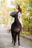 女孩在看她的一匹黑马乘坐 外面 库存照片