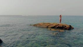 女孩在石头中间清楚的大海站立反对小船 股票录像