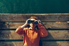 女孩在码头说谎在海附近并且通过双筒望远镜看 旅行查寻旅途概念 免版税图库摄影