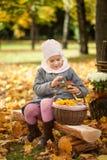 女孩在秋天公园坐一个长木凳在篱芭附近 免版税库存照片