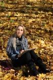 女孩在秋天公园画 库存图片