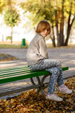 女孩在秋天坐长凳公园 库存图片