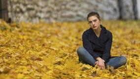 女孩在秋天城市公园坐下落的叶子 免版税库存照片