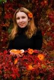 女孩在秋天庭院里 库存图片