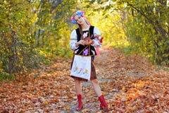 女孩在秋天森林里站立 免版税库存照片