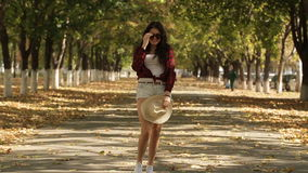 女孩在秋天胡同,微笑对照相机的女孩走 股票录像
