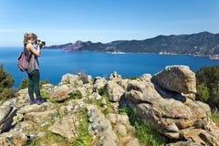 女孩在科西嘉岛拍海湾波尔图的照片 库存图片